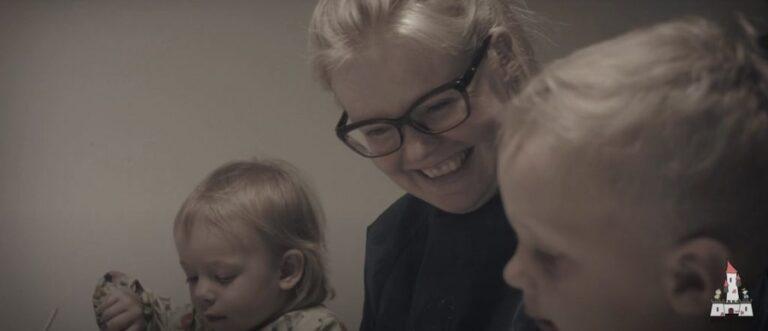 ansat smiler med to børn